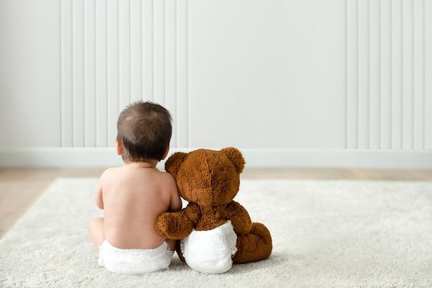 Achteraanzicht van baby en teddybeer met ontwerpruimte