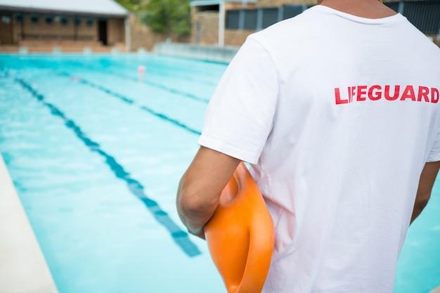 Achteraanzicht van badmeester die zich met reddingsboei dichtbij zwembad bevindt