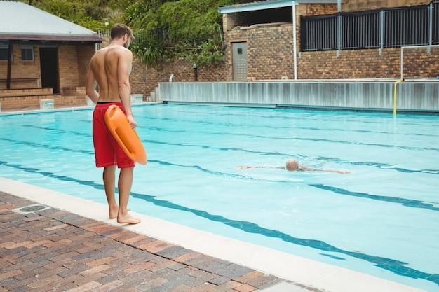 Achteraanzicht van badmeester springen in een zwembad om verdrinkende senior man te redden