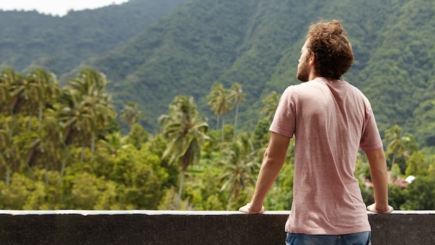 Achteraanzicht van bebaarde reiziger man overweegt schoonheden van groene bossen tijdens vakanties doorbrengen in warm land, genietend van schilderachtig landschap en frisse berglucht