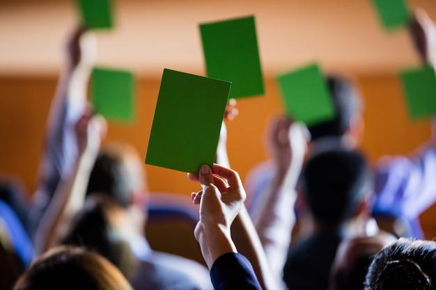 Achteraanzicht van bedrijfsleiders tonen hun goedkeuring door handen op te steken