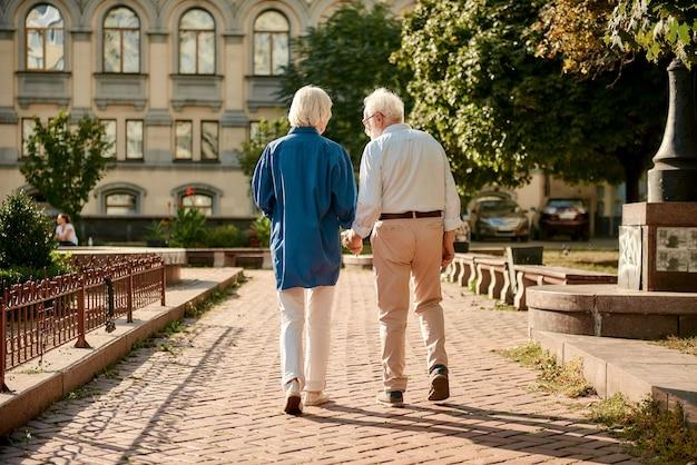Achteraanzicht van bejaarde echtpaar hand in hand terwijl ze samen buiten wandelen