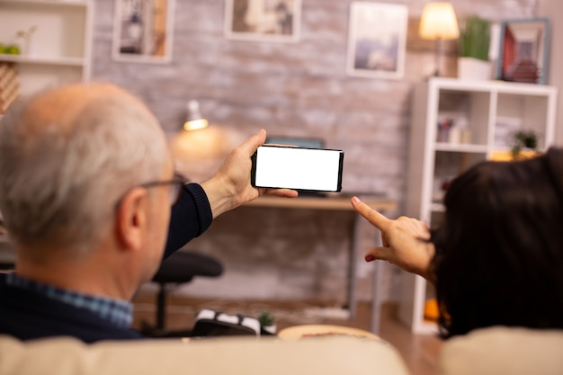 Achteraanzicht van bejaarde gepensioneerd echtpaar kijken naar een smartphone met wit geïsoleerd scherm.