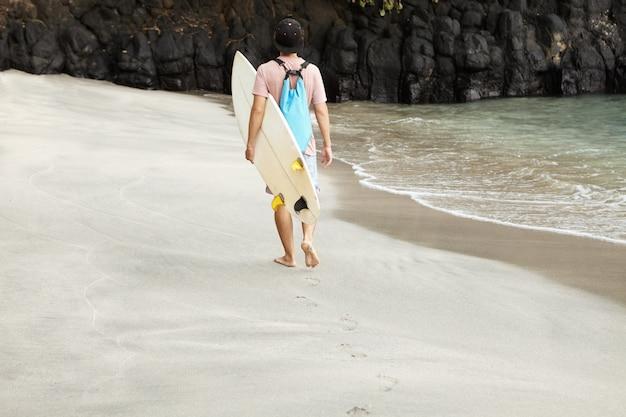 Achteraanzicht van blanke blote voeten surfer met surfplank tijdens het wandelen langs het strand met rotsachtige kust, op weg naar surfen plek