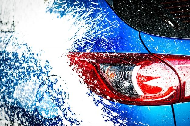 Achteraanzicht van blauwe compacte suv-auto met sport en modern design wassen met zeep