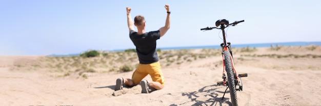 Achteraanzicht van blij opgewonden winnaar reiziger knielt neer met opgeheven handen naast hem is fiets