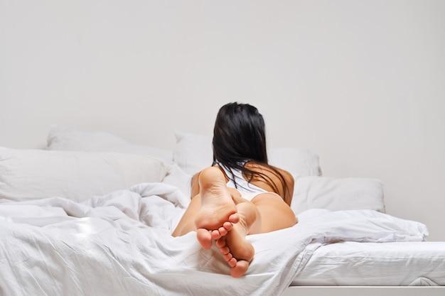 Achteraanzicht van blote voeten vrouw liggend in bed (focus op zolen)