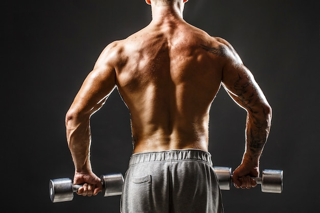 Achteraanzicht van bodybuilder training met halter geïsoleerd op zwarte muur