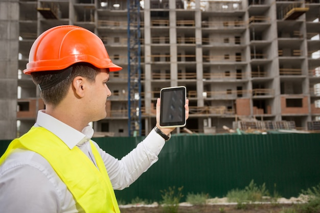 Achteraanzicht van bouwingenieur die de bouwconstructie bestuurt met digitale tablet