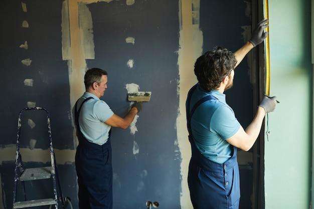 Achteraanzicht van bouwploeg die in de kamer werkt tijdens het bouwen of renoveren van huis, kopie ruimte Premium Foto