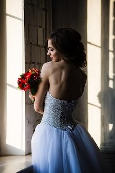 Achteraanzicht van bruid silhouet in de buurt van het raam ruikt de rode bloemen