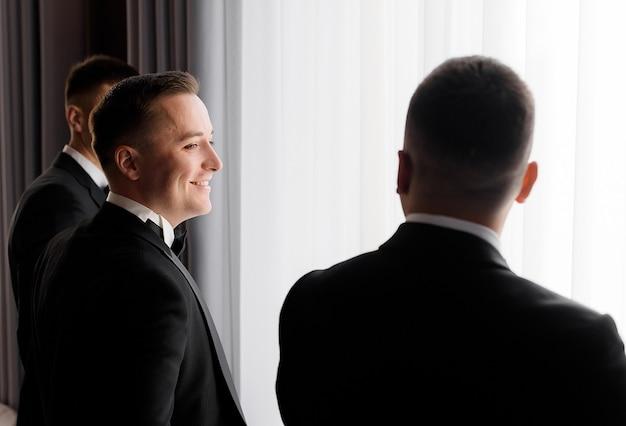 Achteraanzicht van bruidegom en zijn vrienden wachten op de huwelijksceremonie in de hotelkamer