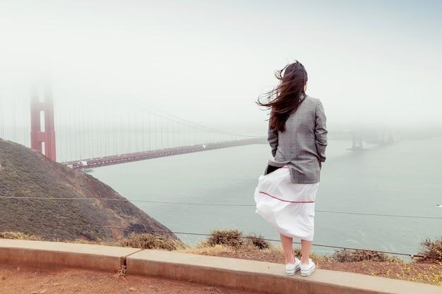 Achteraanzicht van brunette meisje met lang haar in jasje en rok. vrouw staat op een heuvel in mistig winderig weer