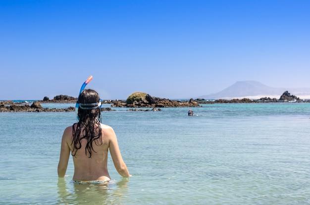 Achteraanzicht van brunette vrouw dragen snorkel en masker op zoek naar de oceaan