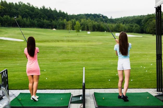 Achteraanzicht van casual meisjes op een golf veld