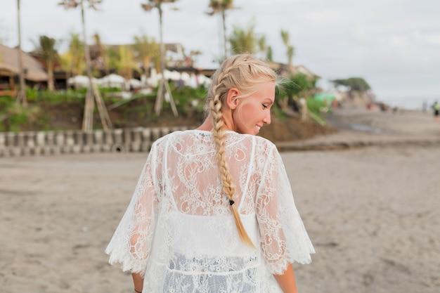 Achteraanzicht van charmante vrouw met blond in witte blouse lopend langs het strand