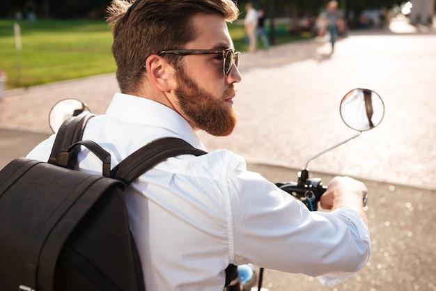 Achteraanzicht van cool bebaarde man in zonnebril met rugzak rijdt op moderne motor buitenshuis en wegkijken
