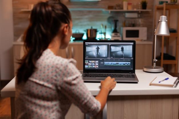 Achteraanzicht van creatieve filmmaker die om middernacht aan een film op laptop werkt