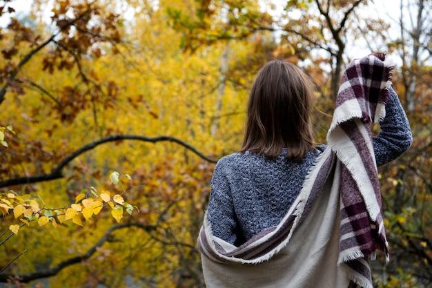 Achteraanzicht van de achterkant van een meisje in een grijze jurk, die is gewikkeld in een sjaal of een sjaal, zet ze haar rechterhand op en kijkt naar het bos met gele bladeren