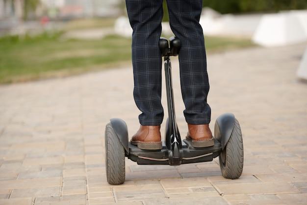 Achteraanzicht van de benen van de jonge hedendaagse man in broek en laarzen die zich op de gyroscoop bevinden terwijl u op weg bent naar het zakencentrum