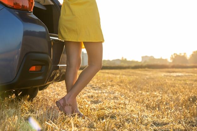 Achteraanzicht van de benen van de jonge vrouw bestuurder in gele zomerjurk staande in de buurt van haar auto.