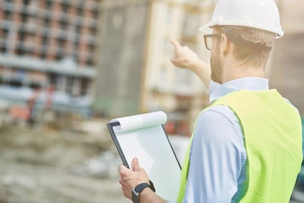 Achteraanzicht van de bouwindustrie van een jonge civiel ingenieur of bouwsupervisor die een helm draagt