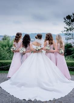 Achteraanzicht van de bruid in trouwjurk en bruidsmeisjes gekleed op de zelfde roze jurken buitenshuis