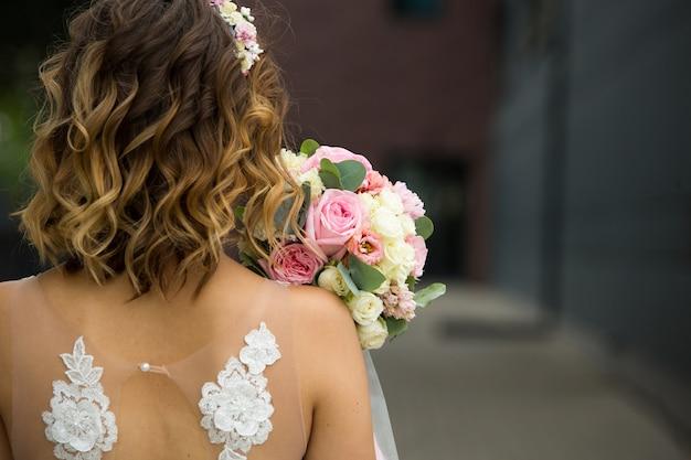 Achteraanzicht van de bruid met boeket bloemen