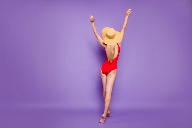 Achteraanzicht van de dame die zich op zand naar de zee verplaatst, geïsoleerd violet paarse kleur