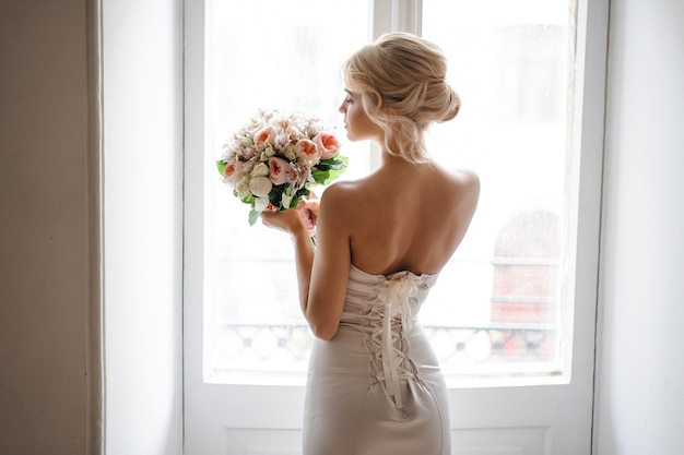 Achteraanzicht van de elegante blonde bruid gekleed in een witte jurk met een bruiloft boeket