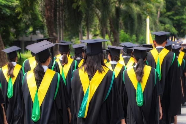 Achteraanzicht van de groep van universitair afgestudeerden in zwarte jassen op een rij voor diploma in universitaire diploma-uitreiking.