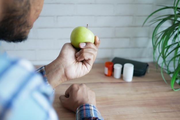 Achteraanzicht van de hand van de jonge man met groene appel