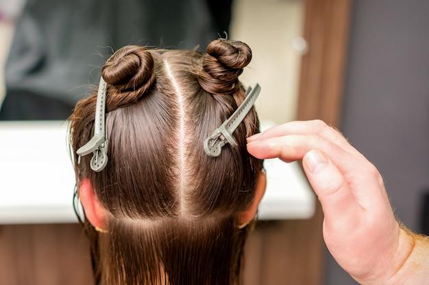 Achteraanzicht van de hand van de kapper die kapsel van jonge vrouw met haarclips op haar haar in de kapsalon doet