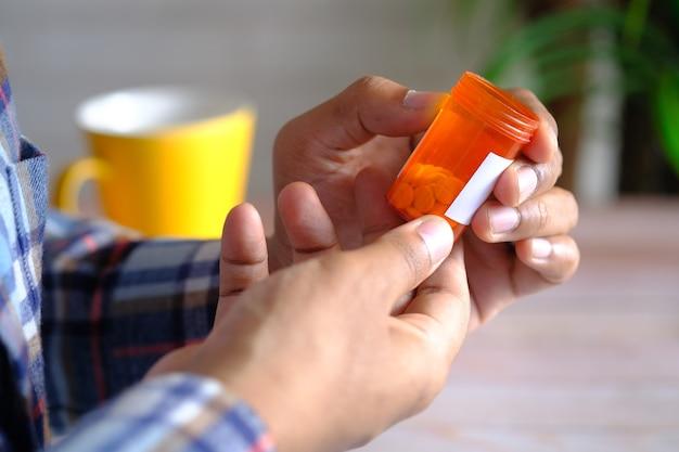 Achteraanzicht van de hand van een jonge man houdt een container voor medische pillen vast