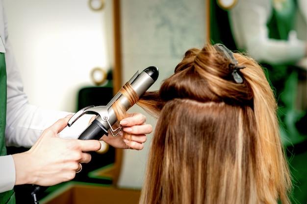 Achteraanzicht van de handen van de vrouwelijke kapper die het haar van vrouwen met krultang in een kapsalon krullen