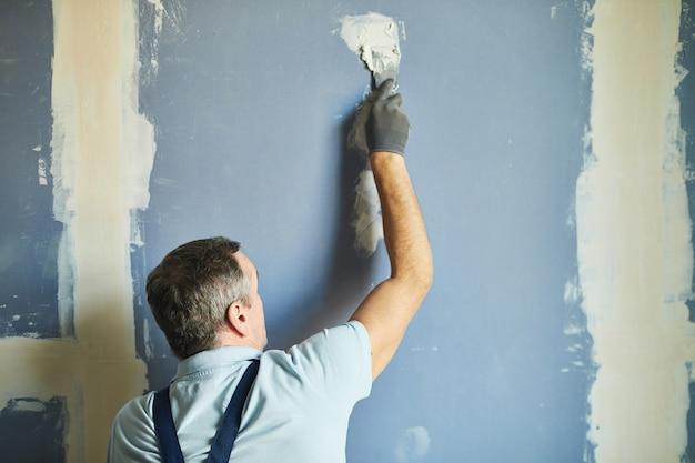 Achteraanzicht van de hoge sectie van senior bouwvakker droge muur gladstrijken tijdens het renoveren van huis, kopieer ruimte