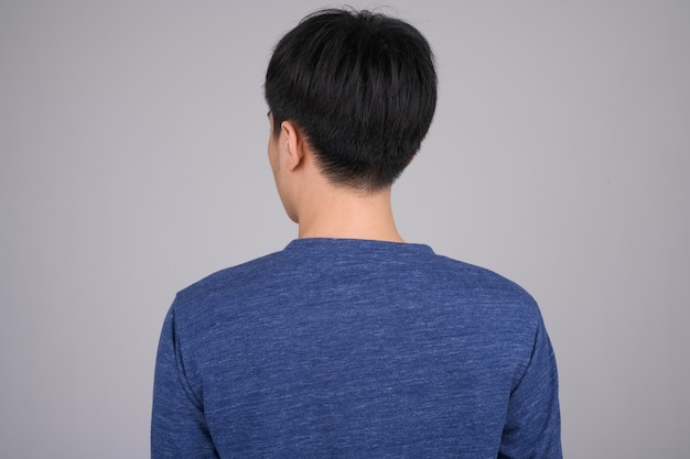 Achteraanzicht van de jonge aziatische man op wit