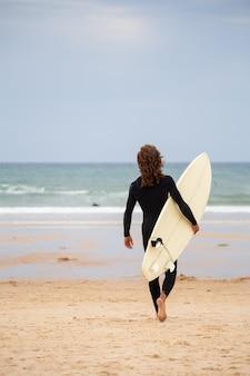Achteraanzicht van de jonge man in zwarte wetsuit lopen naar zee met surfplank