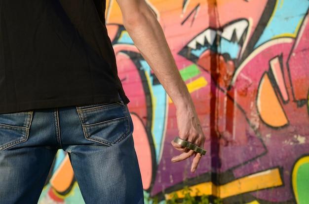 Achteraanzicht van de jonge man met koperen cnuckle op zijn hand tegen gettobakstenen muur
