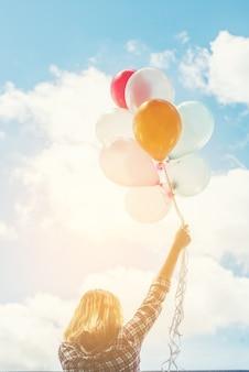Achteraanzicht van de jonge vrouw met kleurrijke ballonnen