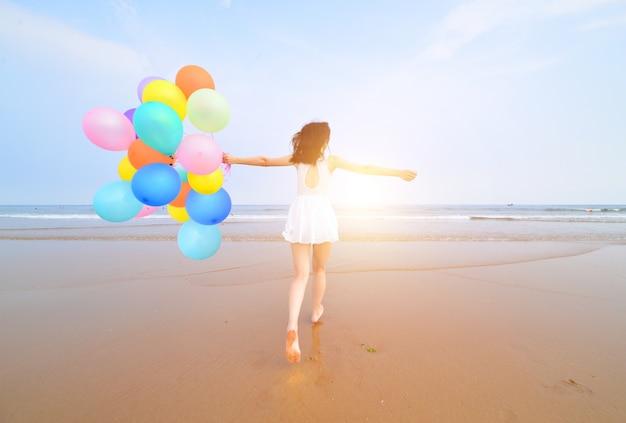Achteraanzicht van de jonge vrouw viert haar verjaardag op het strand