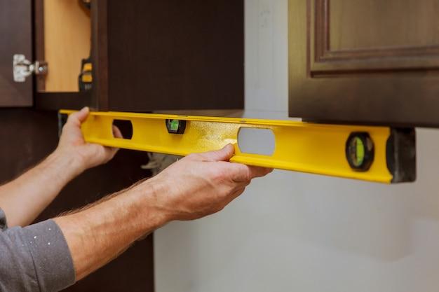 Achteraanzicht van de keuken van de reparateur bevestigende kast