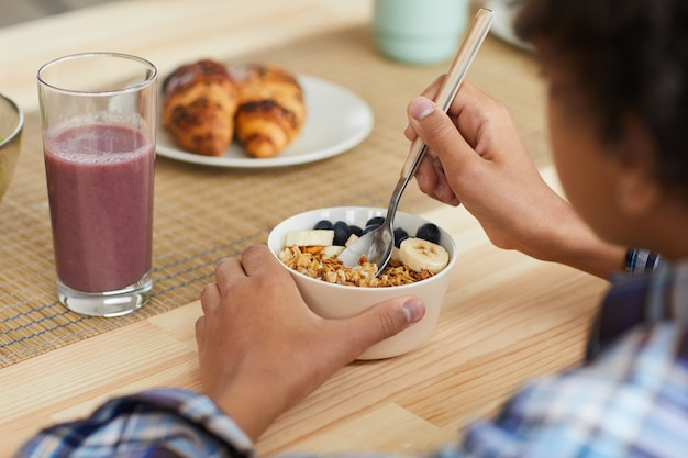 Achteraanzicht van de kleine jongen aan de tafel zitten en granen met bessen eten en vers sap drinken heeft hij ontbijt