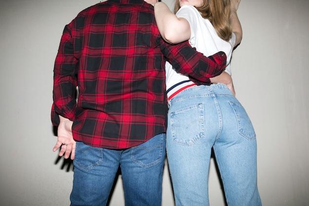 Achteraanzicht van de lage hoek van gewas jonge vriend en vriendin stijlvolle kleding dragen knuffelen op grijze achtergrond in de studio