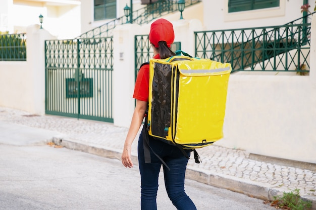 Achteraanzicht van de levering vrouw met gele thermo tas. ervaren koerier die buiten op straat loopt en bestelling levert.