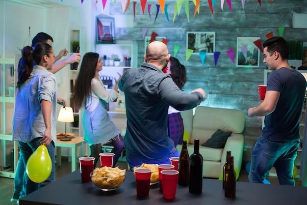 Achteraanzicht van de man die danst met zijn vrienden die plezier hebben met feesten. chips en ballonnen.