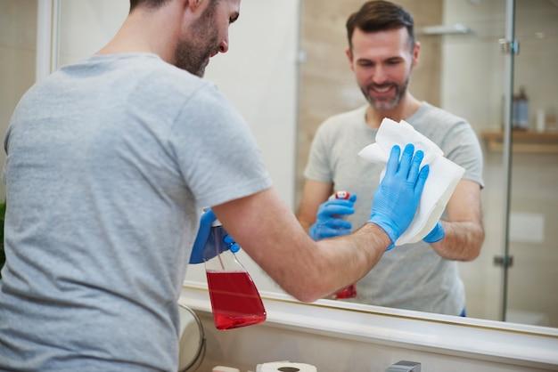 Achteraanzicht van de man die de spiegel in de badkamer schoonmaakt