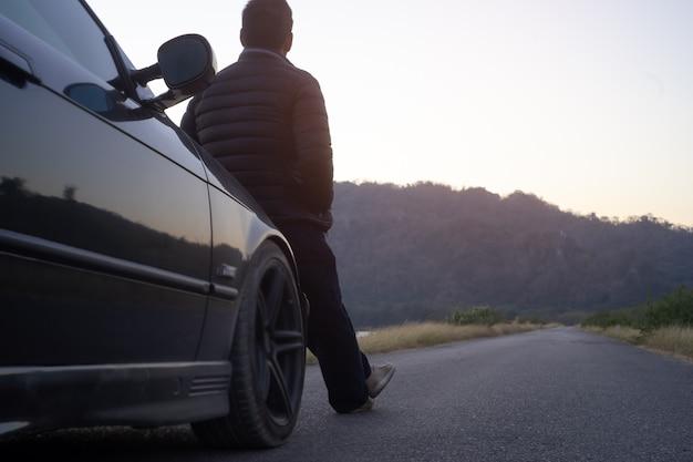 Achteraanzicht van de man die voor de auto zit en geniet van de zonsondergang