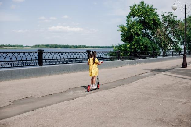 Achteraanzicht van de meisjes die terug vertrekken op een scooter langs het pad langs de rivier de volga zomeractiviteiten