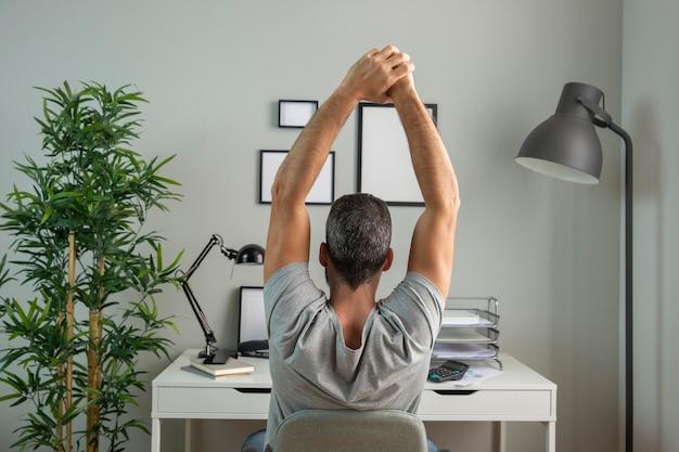 Achteraanzicht van de mens aan het bureau dat zich uitstrekt tijdens het werken vanuit huis
